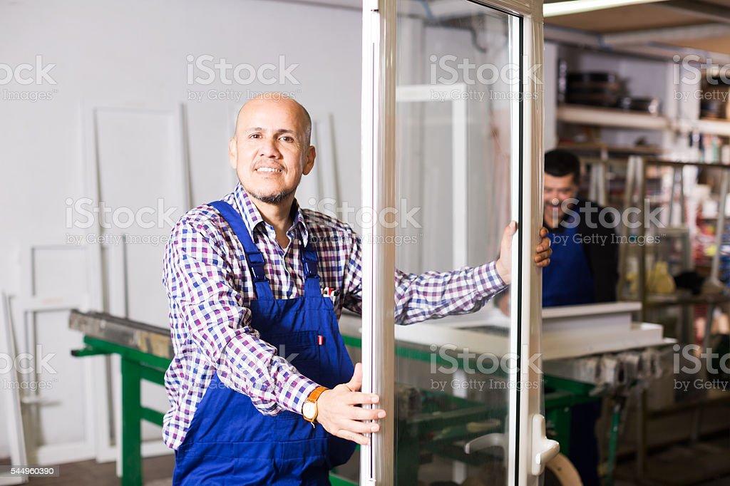 labours produce PVC profiles and windows stock photo