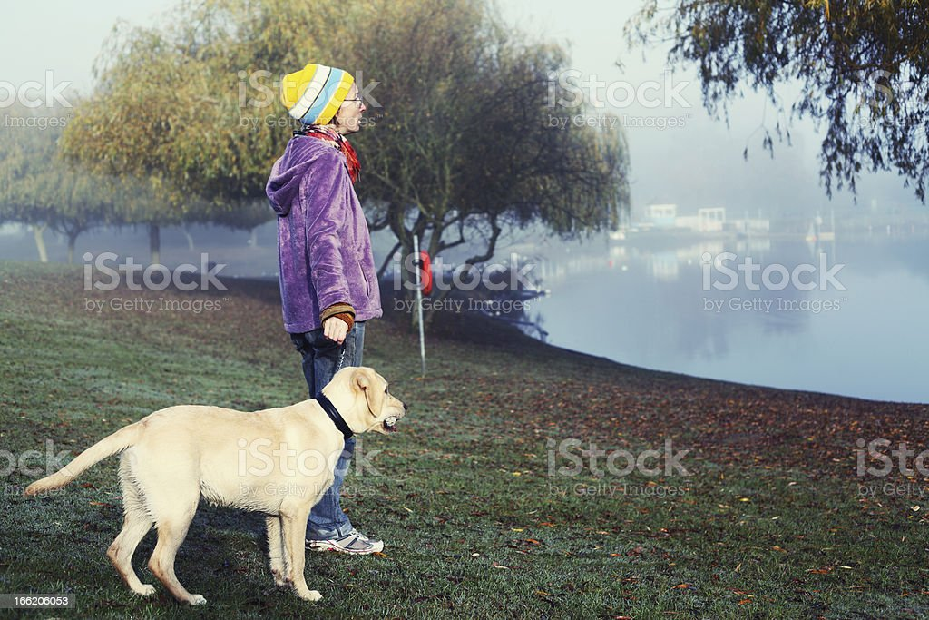 Labrador and owner standing by a lake stock photo