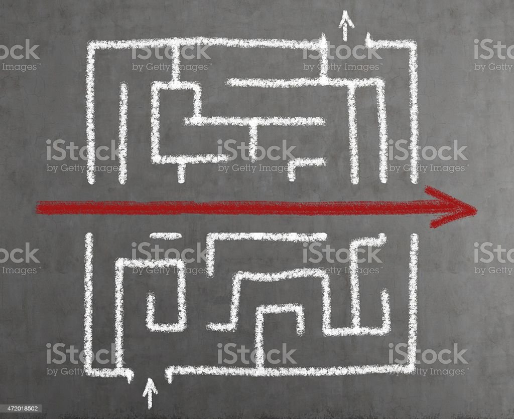 Labyrinth drawn on blackboard with red arrow stock photo