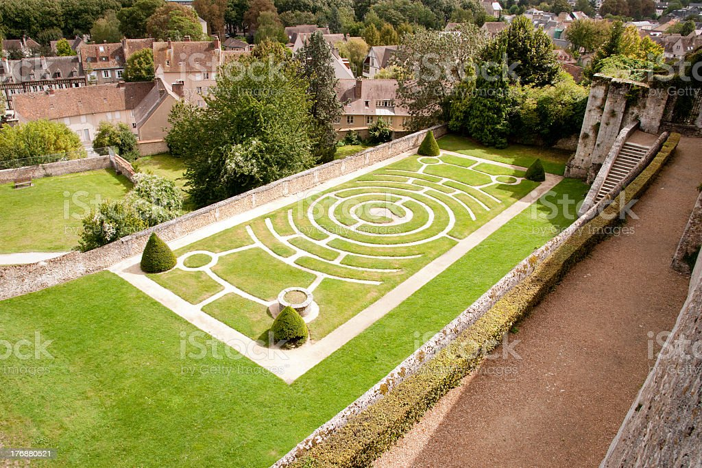 A labyrinth garden design set next to some buildings stock photo