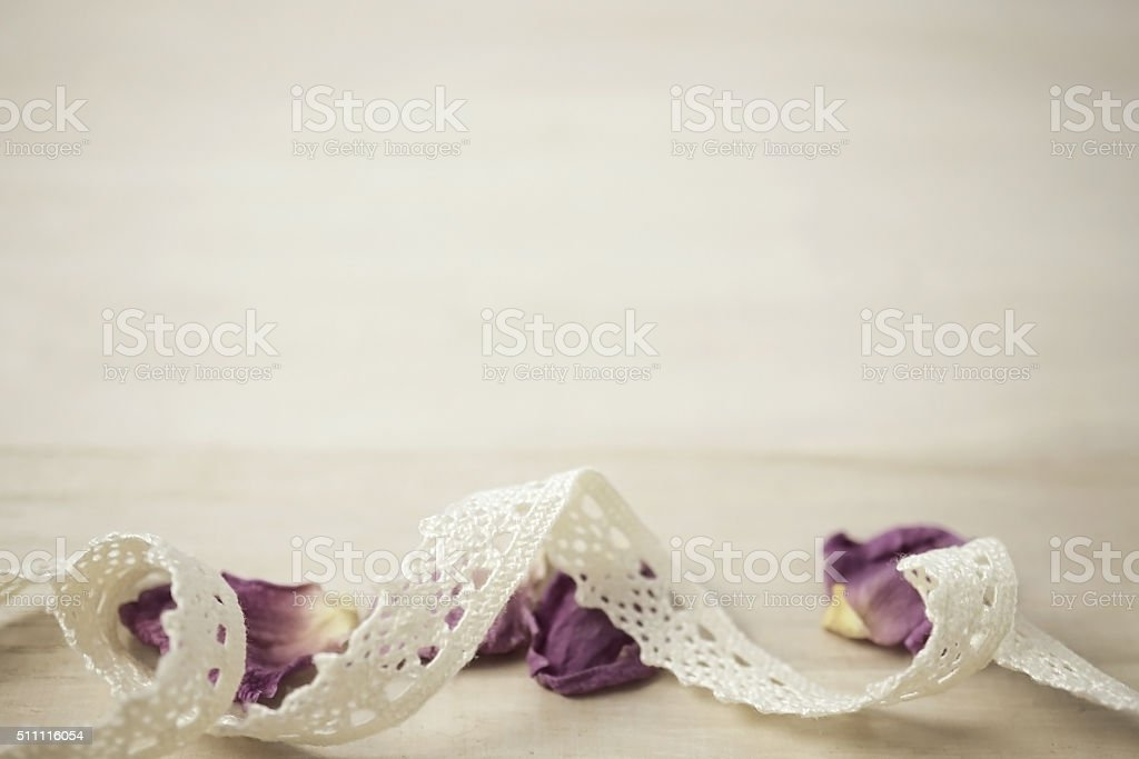 lace and dried rose petals on wooden background stock photo