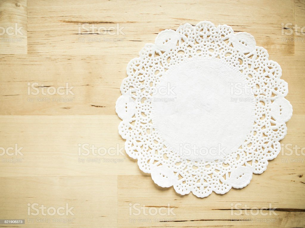 Lace paper on wooden table stock photo
