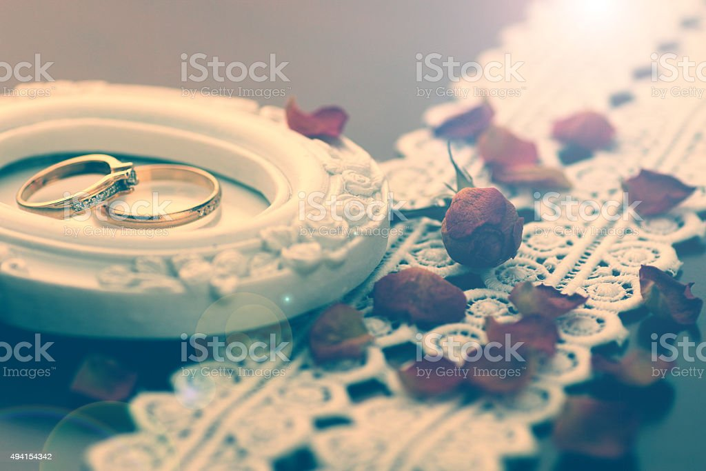 lace wedding rings petals stock photo