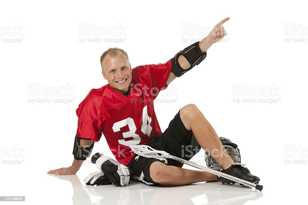 Lacrosse player sitting on the floor and pointing royalty-free stock photo