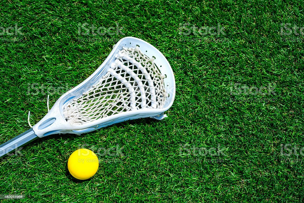 Lacrosse stick and ball on artificial turf stock photo