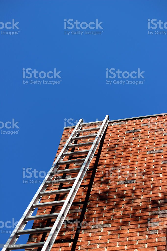 Ladder Against a Brick Chimney with Blue Sky Background stock photo