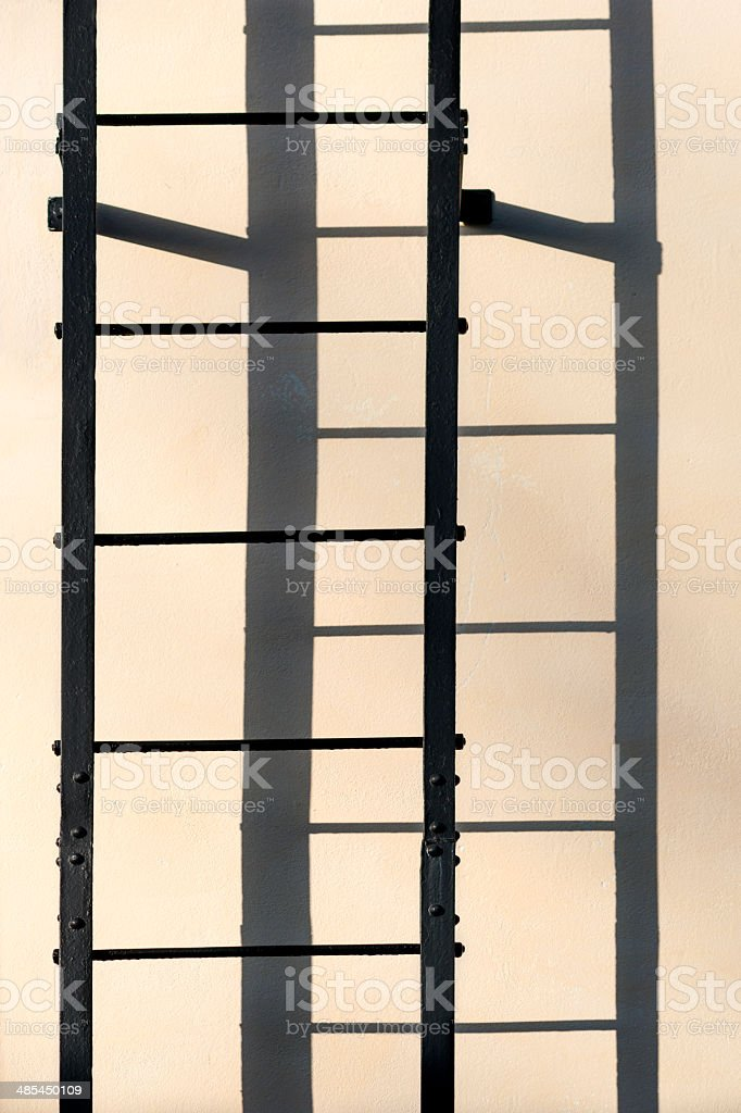 Ladder casting shadow on wall stock photo