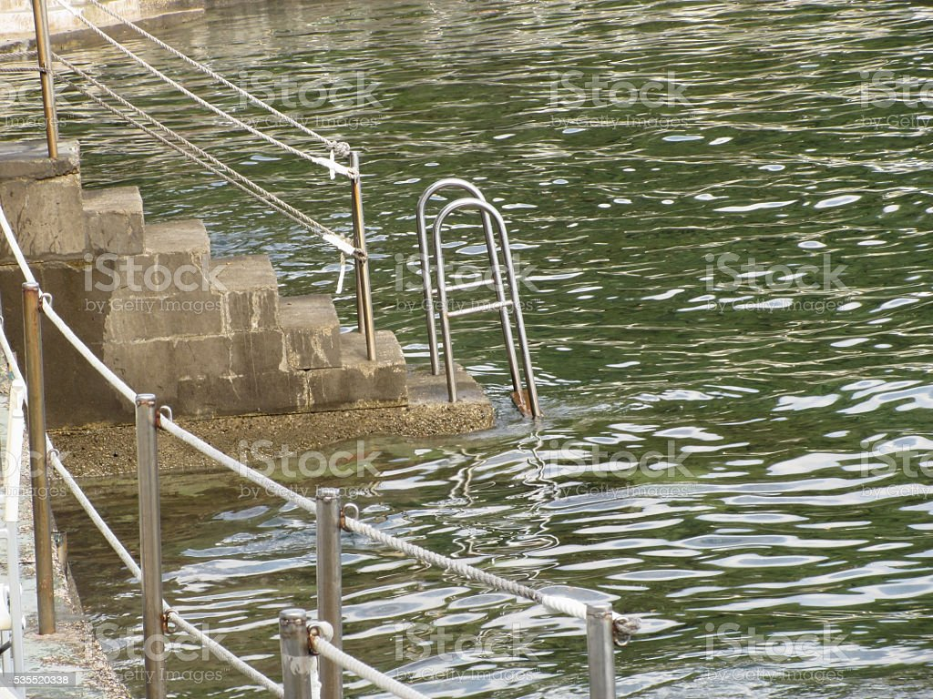 Ladder descending into the sea water . Tuscany, Italy stock photo
