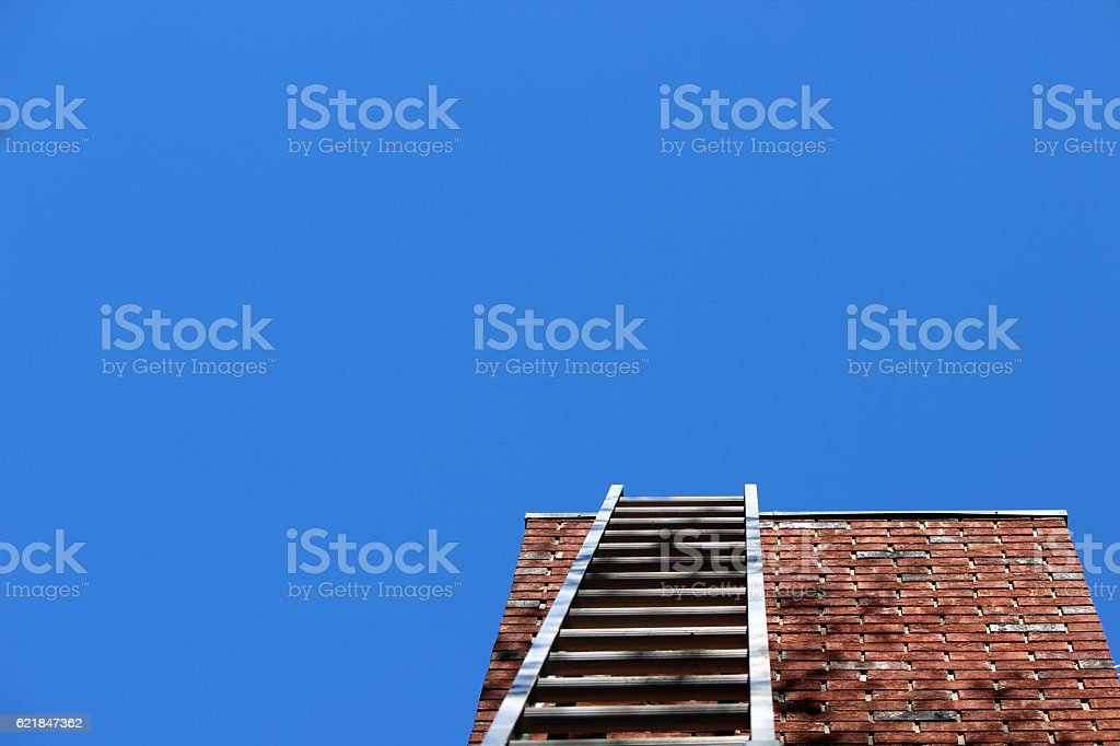 Ladder Leaned on Brick Chimney with Blue Sky Background stock photo