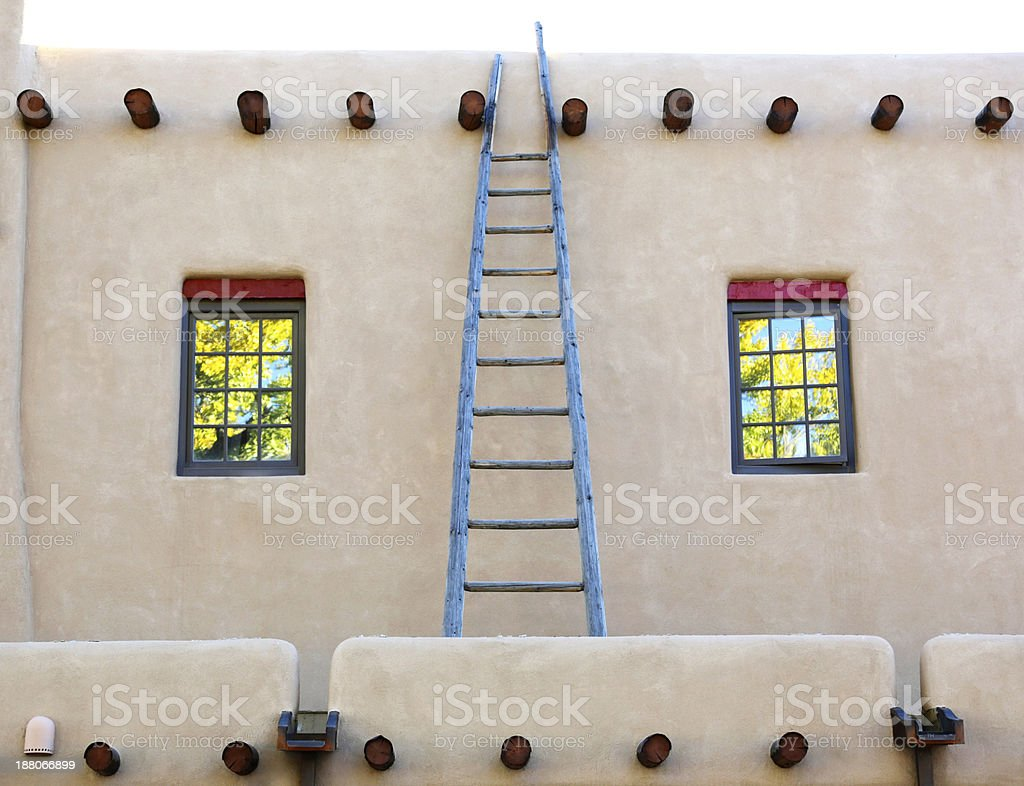 Ladder on adobe house with window reflections of trees royalty-free stock photo