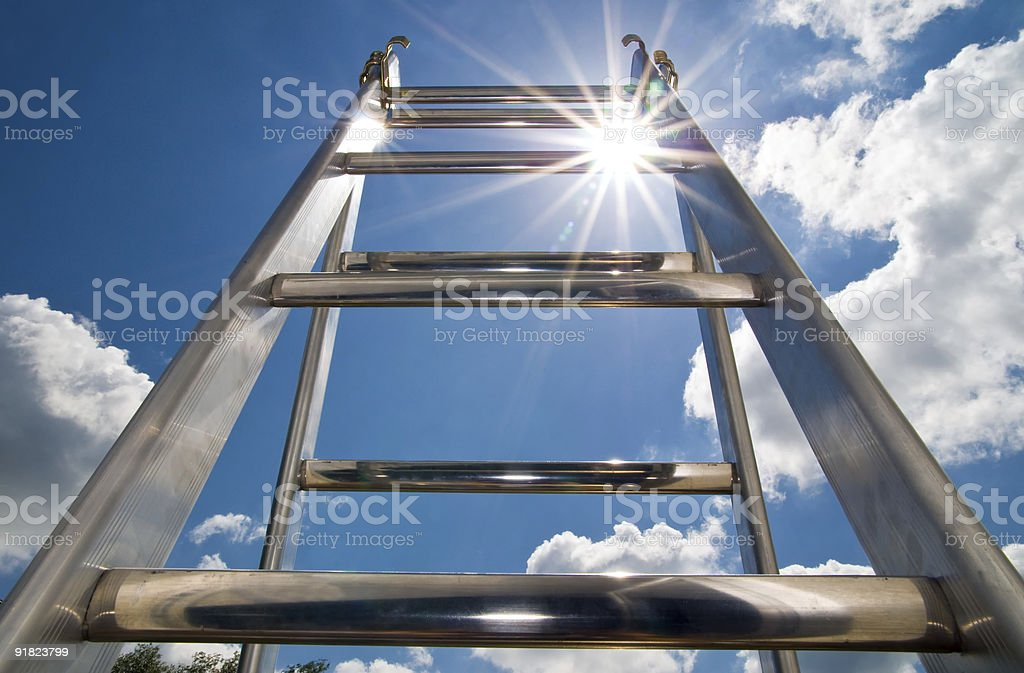 A ladder outside in the sun and clouds stock photo