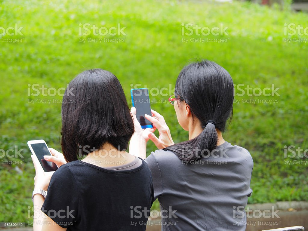 Ladies Are Watching The Screen Of their Smartphone stock photo