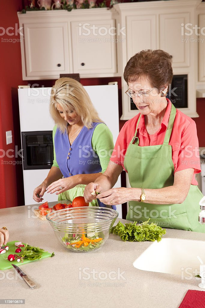 Ladies in the kitchen preparing salad for a luncheon royalty-free stock photo
