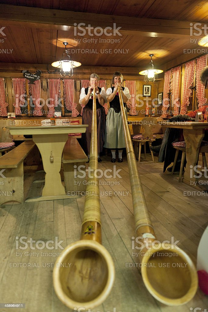ladies in traditional clothing playing alpenhorn stock photo