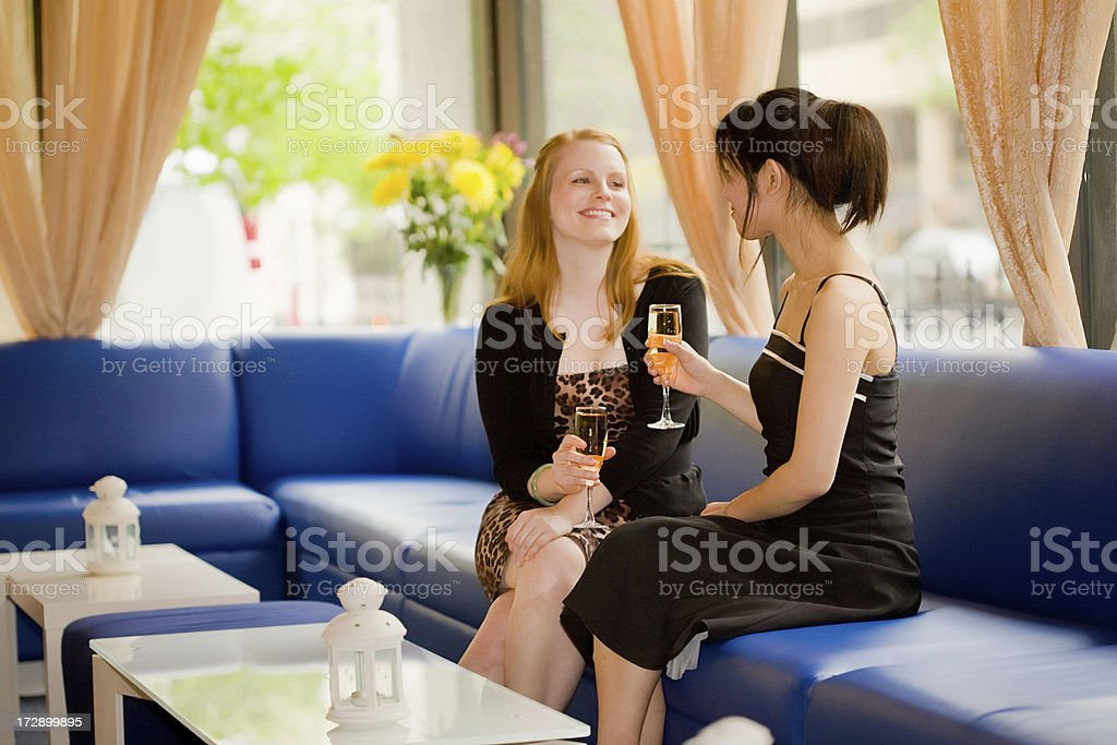Ladies laugh and chat over champagne royalty-free stock photo