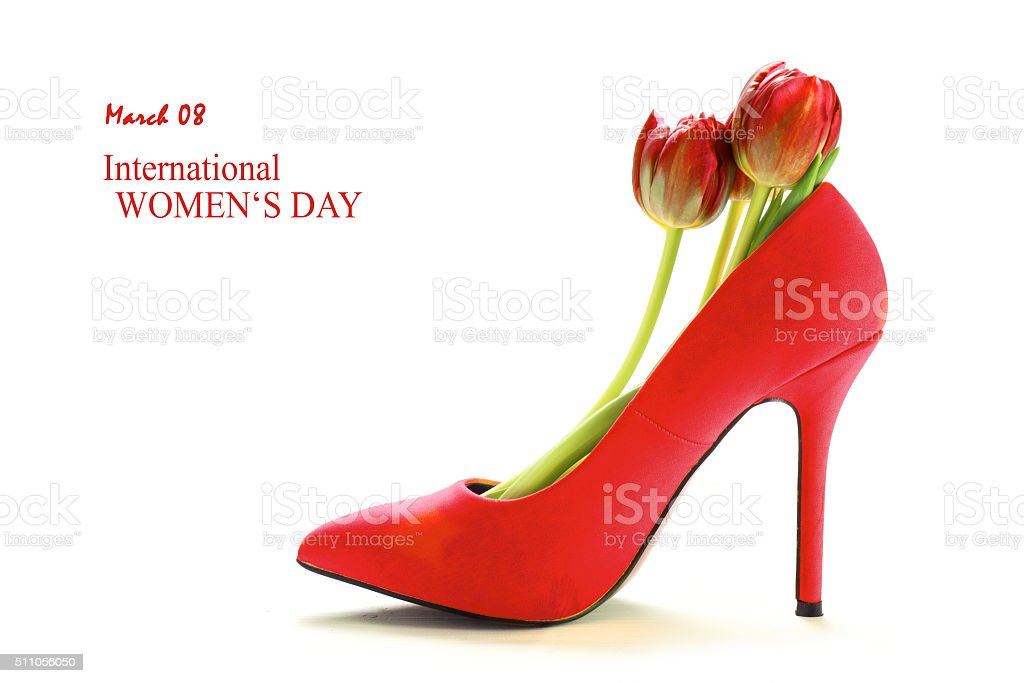 Ladies red shoe with tulips isolated on white, womens day stock photo