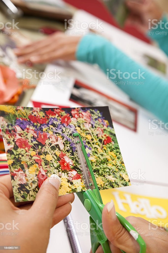 Ladies scrapbooking, cutting photographs to desired sizes. royalty-free stock photo