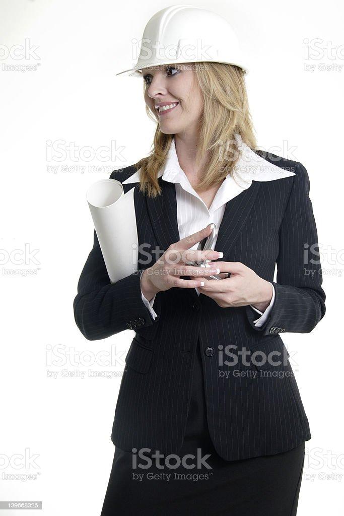 Lady architect holding blue prints wearing a white hard hat royalty-free stock photo