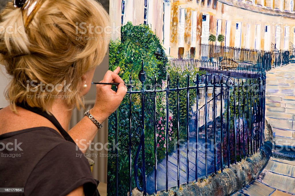 Lady artist at work painting a large acrylic artwork stock photo