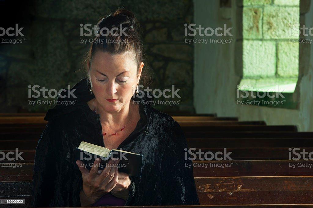 Lady at prayer stock photo