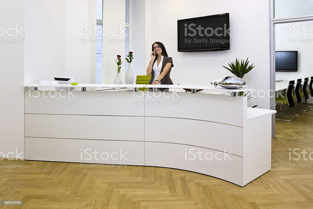 Lady at the front desk enjoys her job stock photo