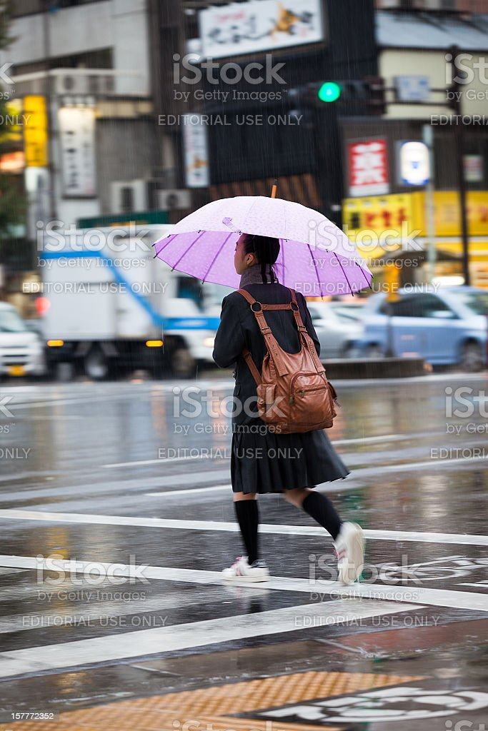 Lady crossing the street with umbrella on a rainy day stock photo