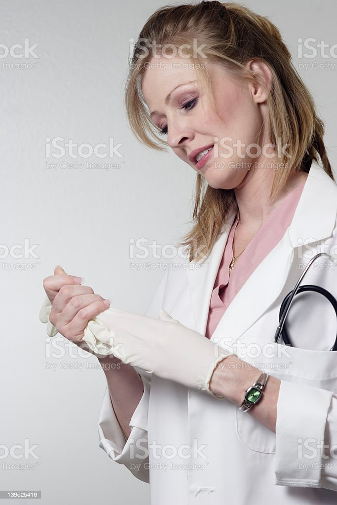 Lady Doc removing rubber gloves royalty-free stock photo