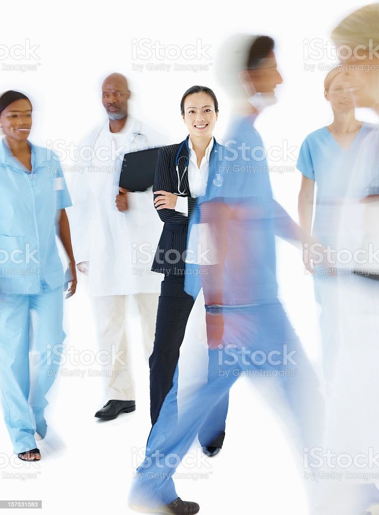 Lady doctor smiling with blur view of colleagues walking royalty-free stock photo