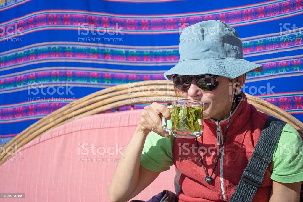 Lady having coca leaves tea, known as 'Mate de Coca' stock photo