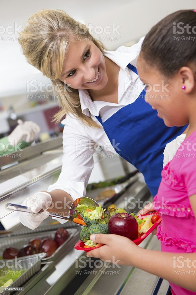 Lady helping little girl with food in the lunch line royalty-free stock photo