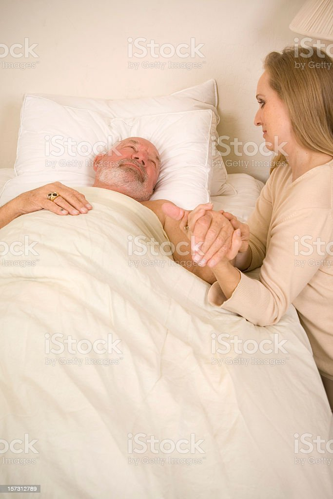 A lady holding an old man's hand who is lying in bed royalty-free stock photo