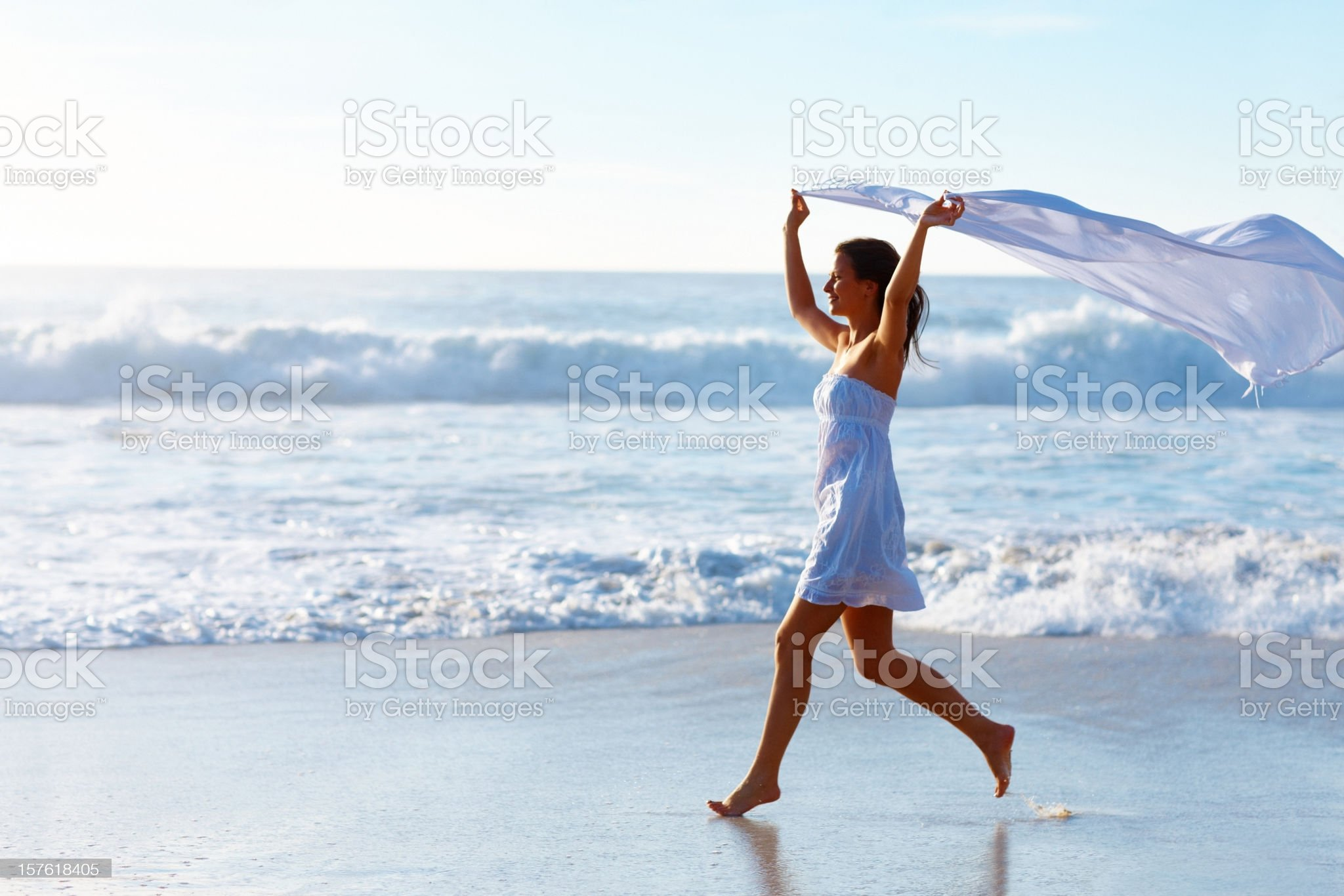 Lady holding stole while running on beach royalty-free stock photo