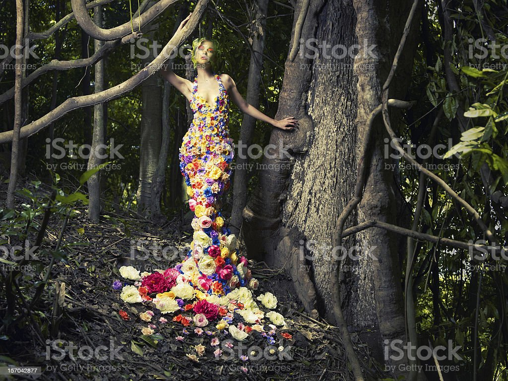 Lady in a dress of flowers posing in a wood stock photo