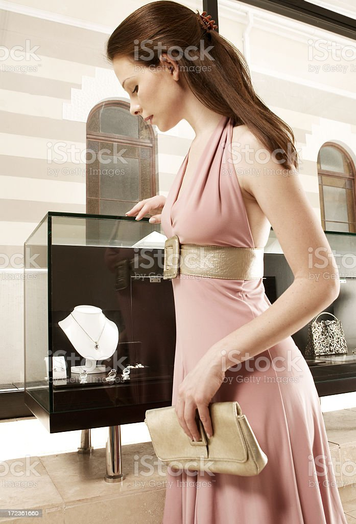 A lady in a pink dress going jewelry shopping stock photo