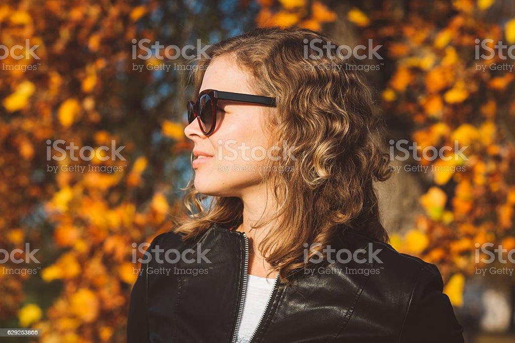 Lady in Autumn Wears Sunglasses stock photo