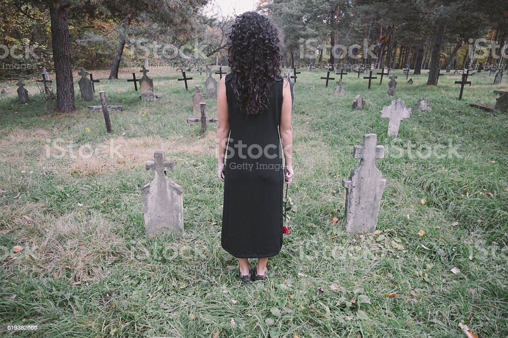 Lady in black dress standing at graveyard. View from behind. stock photo