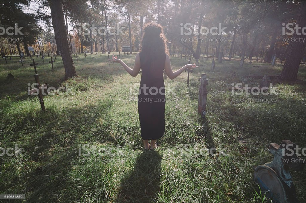 Lady in black dress standing on sunlight at graveyard. stock photo
