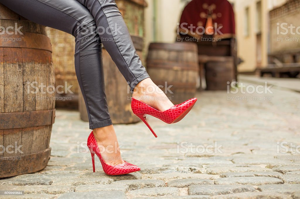 Lady in black leather pants and red high heel shoes stock photo