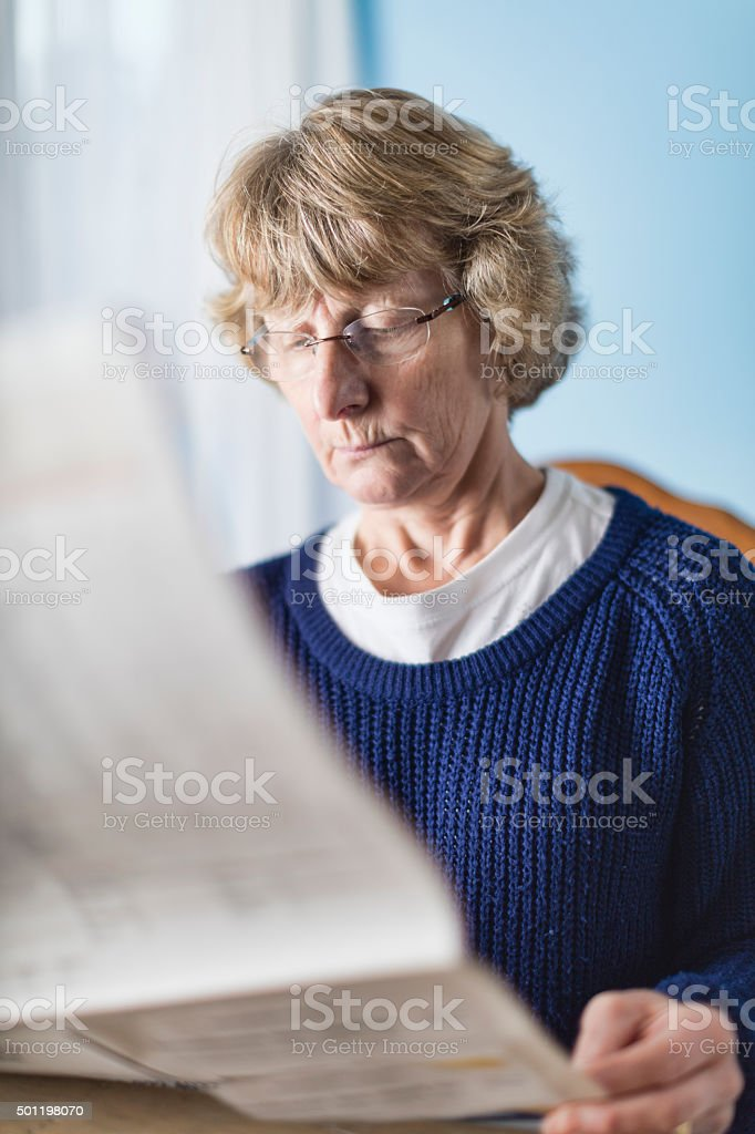 Lady In Her Sixties Reading The Morning Newspaper stock photo