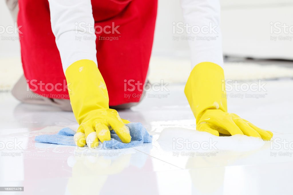 Lady in protective gloves cleaning a floors. stock photo