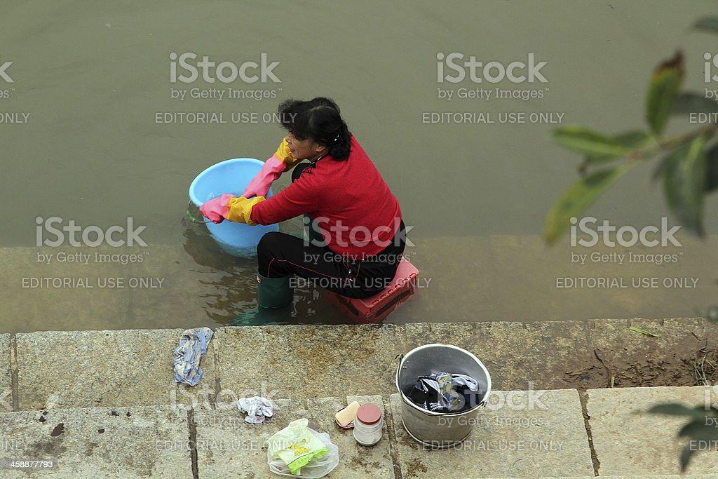La signora in rosso facendo lavanderia a mano, Fiume Ganzhou foto stock royalty-free