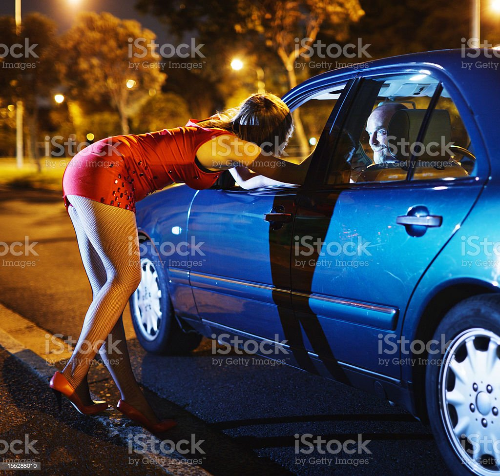 Lady in red: young prostitute negotiates with eager car driver stock photo