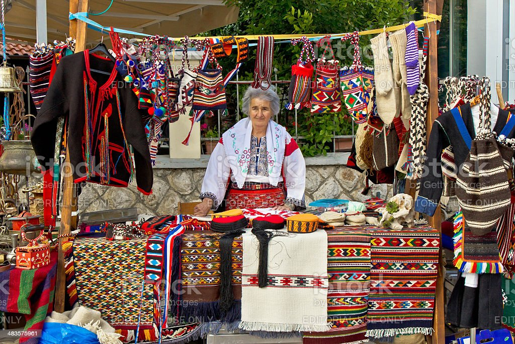 Lady in traditional clothes selling on booth stock photo