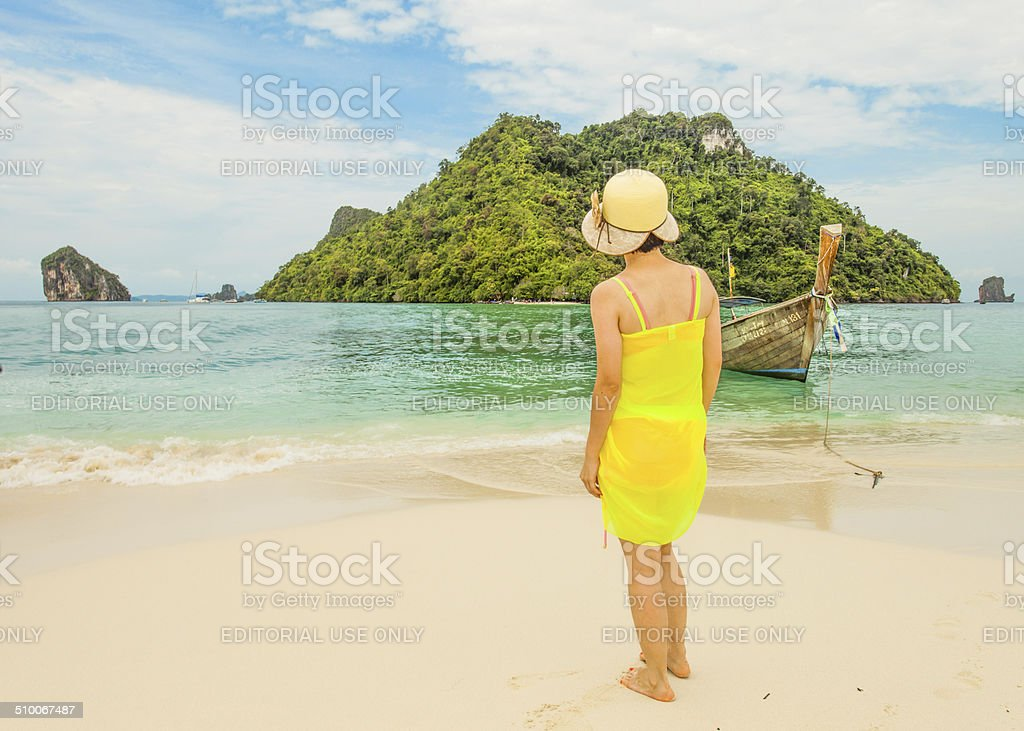 Lady in yellow dress and hat standing on Tup island stock photo