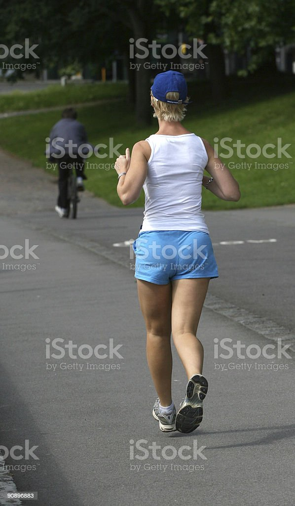 Lady jogger exercising on a track in park stock photo