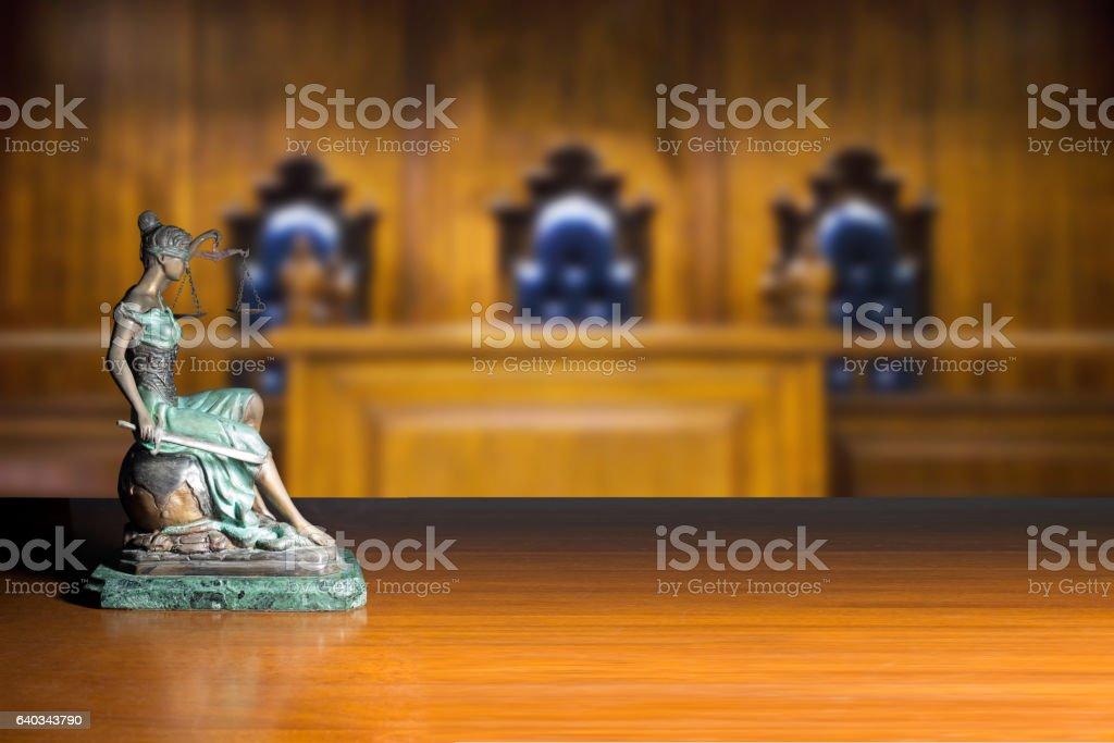 Lady justice and empty bench with judge chairs in courtroom stock photo