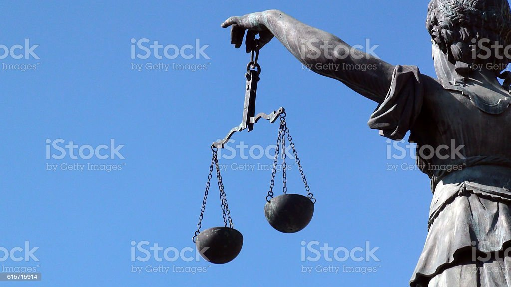 Lady Justice Holding Weight Scale Against Summer Shining Blue Sky stock photo