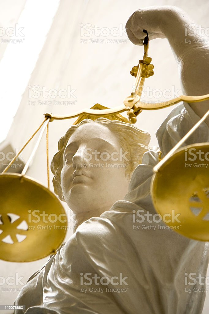 Lady Justice statue holding golden scales stock photo