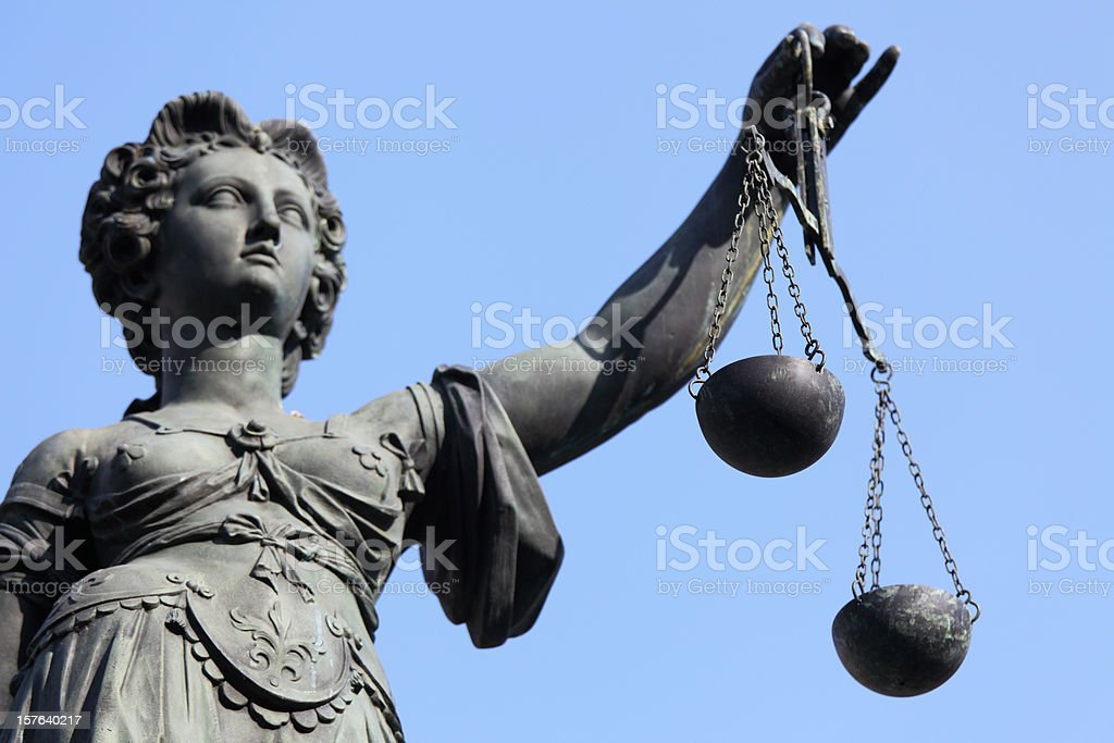 Lady Justice statue with scale against blue sky royalty-free stock photo