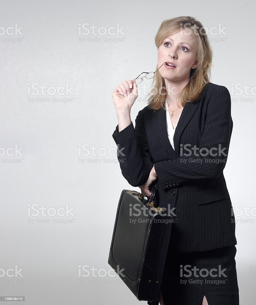 Lady lawyer thinking while holding glasses stock photo